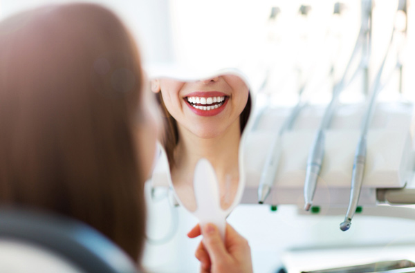 Woman looking at her smile in a mirror after restorative dental treatment from SmileCOS Dentistry